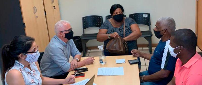 Audiência de conciliação em Itaboraí: cinco pessoas sentadas em torno de mesa